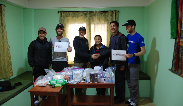Dan, Kay and Andy from Xtreme Everest and University of Nebraska Medical Center hand over donations to the clinic staff
